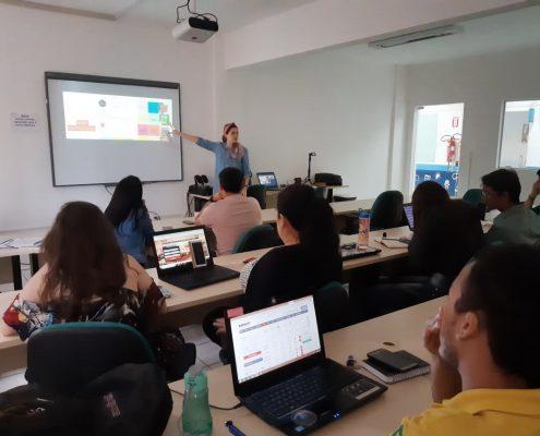 Uma foto de uma sala com alunos e a professora Érika Zuza ministrando uma capacitação de instagram para startups